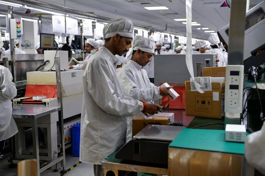 Workers pack mobile phones at an Indian phone manufacturer Lava factory in Noida, on Aug 22, 2019.