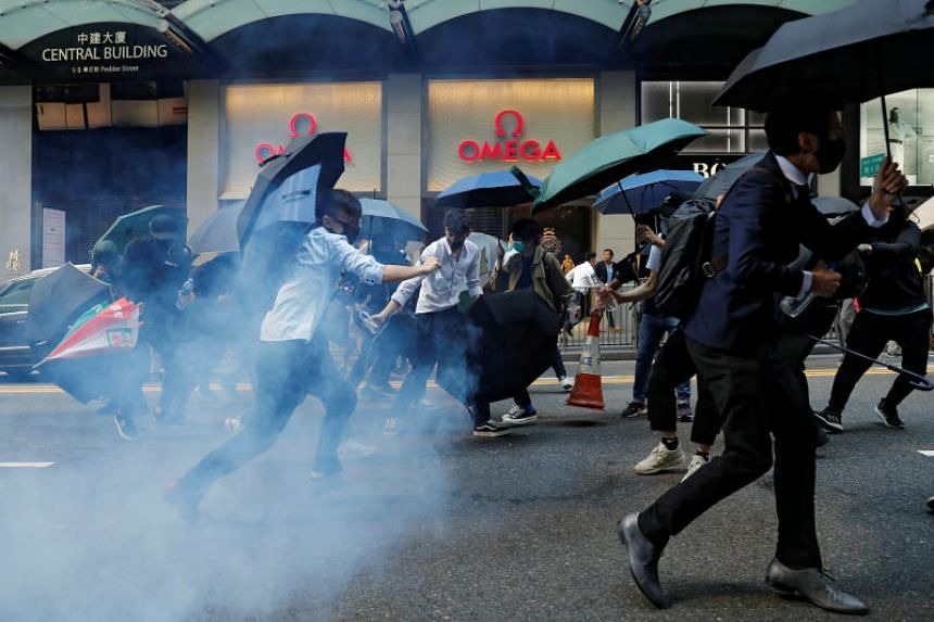 Office workers run away from tear gas as they attend a flash mob anti-government protest at the financial Central district in Hong Kong on Nov 11, 2019.