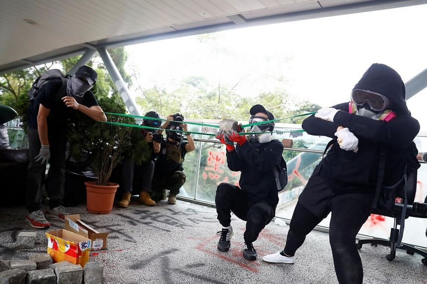Demonstrators using an elastic band to propel a rock on a footbridge during an anti-government protest near City University in Kowloon Tong, Hong Kong, on Nov 12, 2019.