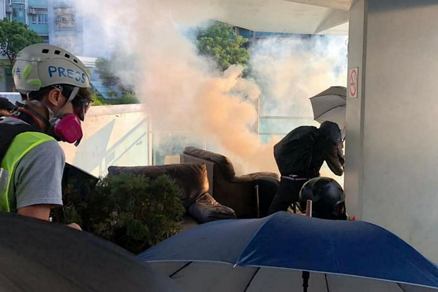Protesters taking cover as police fire tear gas at City University campus.