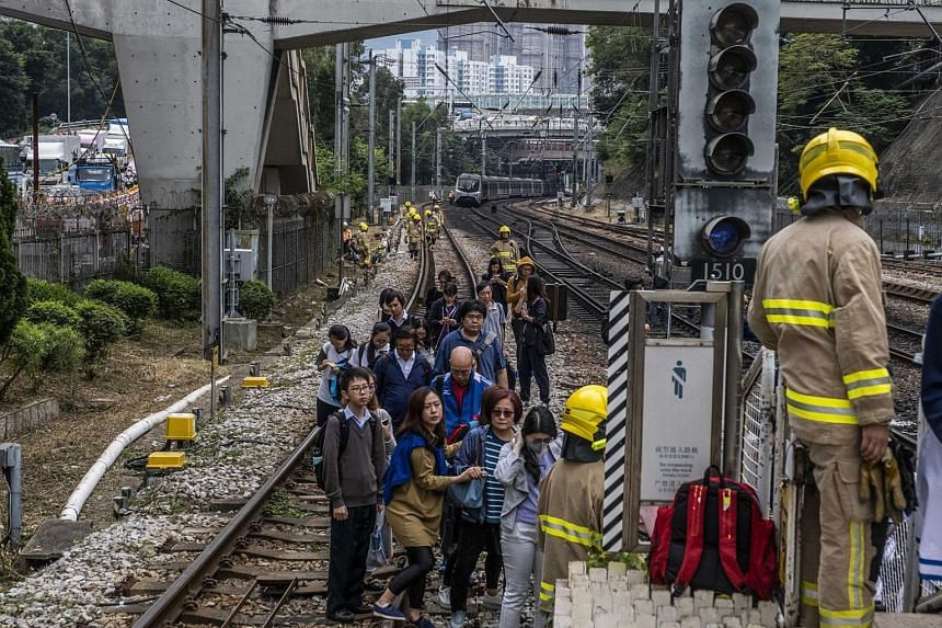 Passengers walking on the railway after train service was suspended in the Sha Tin area of Hong Kong, on Nov 12, 2019.