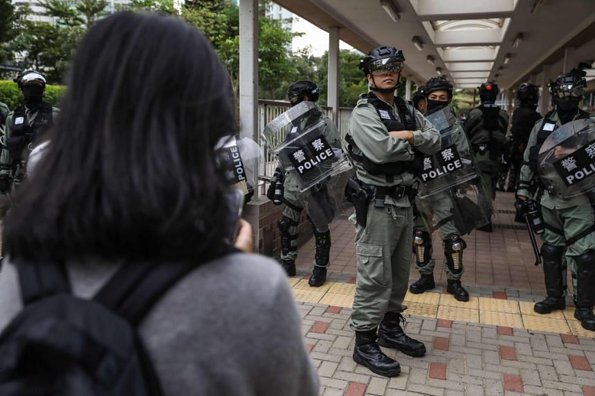 A woman talks to the police in the Sai Wan Ho district in Hong Kong on Nov 11, 2019.