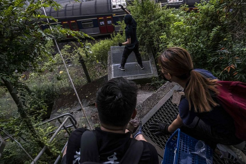 Protesters throwing stones at a railway at the Chinese University of Hong Kong, on Nov 12, 2019.