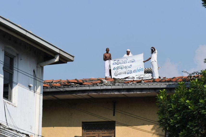 Prisoners display a banner to protest the pardon for Jude Jayamaha on the roof of a building inside the Welikada prison in Colombo on Nov 12, 2019.