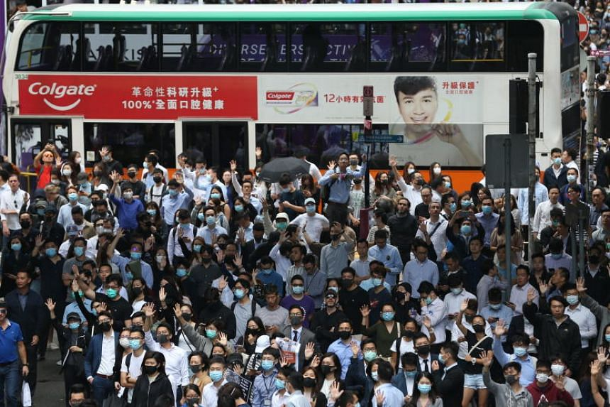 Pro-democracy protesters and office workers blocking a road during a lunchtime flash mob in Central, Hong Kong, on Nov 12, 2019.