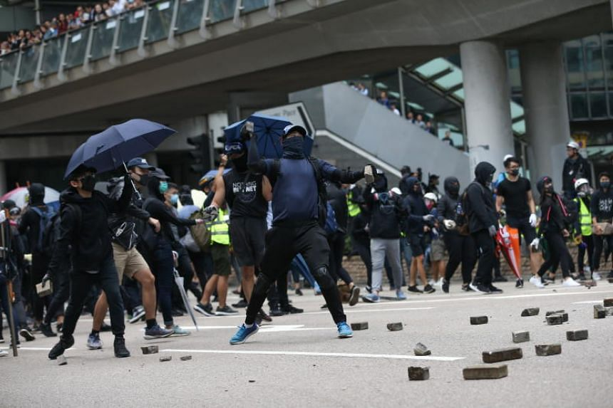 A pro-democracy protester throws stones to block a road during a lunchtime flash mob in Central, Hong Kong, on Nov 12, 2019.