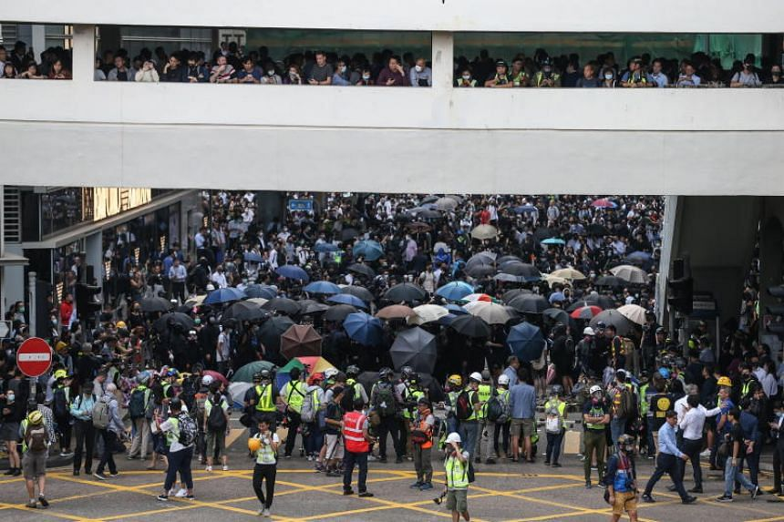 Pro-democracy protesters and office workers block a road during a lunchtime flash mob in Central.