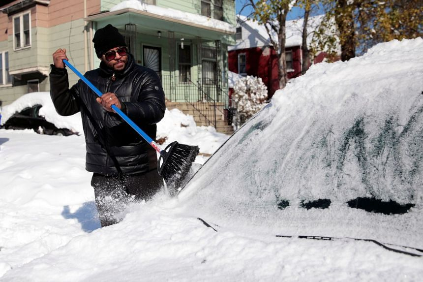 Charles Stevens cleans the snow off his vehicle in Detroit, Michigan.