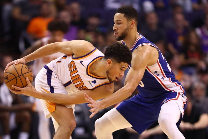 Phoenix Suns guard Devin Booker (left) against Philadelphia 76ers guard Ben Simmons in the second half at Talking Stick Resort Arena.