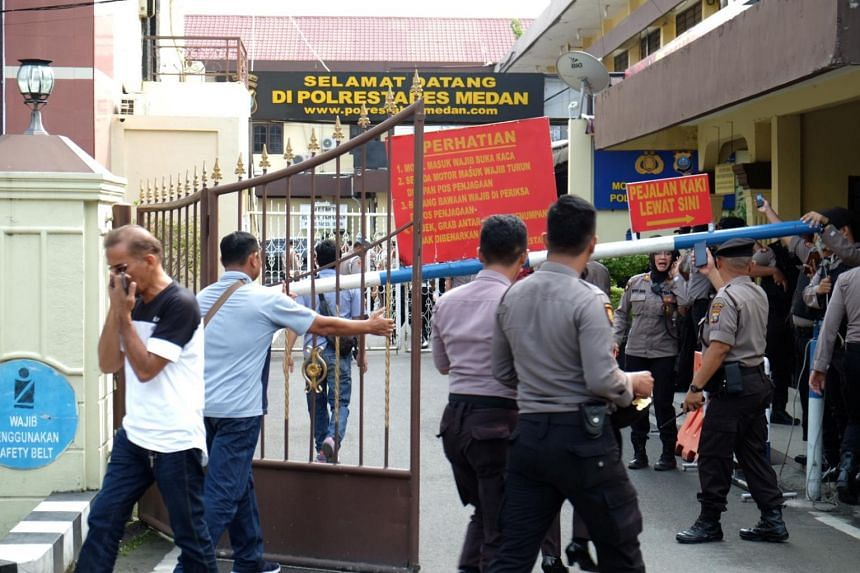 Police officers stand guard at the entrance of the local police headquarters following the blast.
