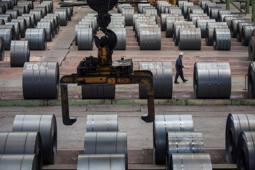 A worker walks past steel rolls at the Chongqing Iron and Steel plant in Changshou, China.