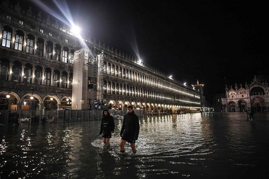 """People walk across the flooded St Mark's Square during an exceptional """"Acqua Alta"""" high tide water level on Nov 12, 2019."""
