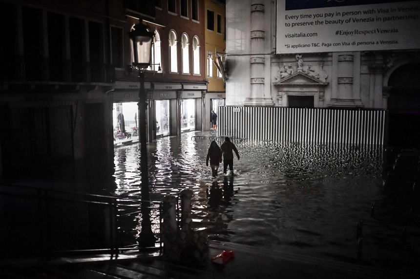 """People walking across the flooded St Mark's Square during an exceptional """"Acqua Alta"""" high tide water level on Nov 12, 2019."""