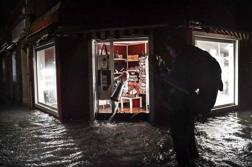 A shop owner clearing his flooded premises on Nov 12, 2019, in Venice.