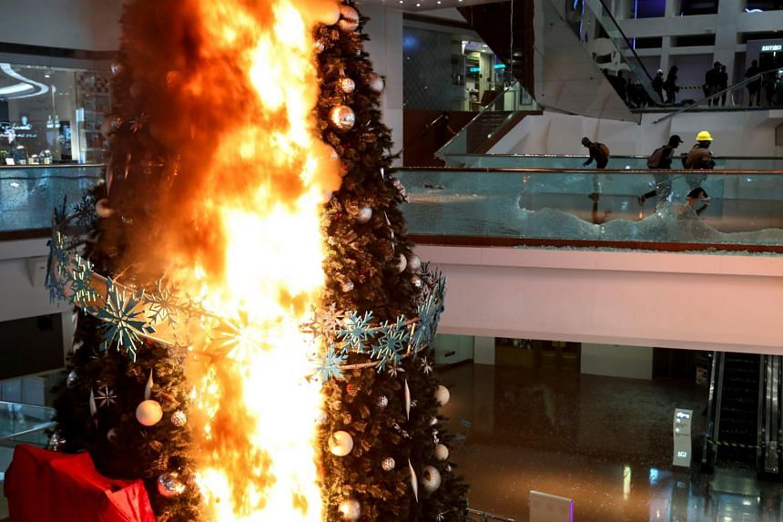 Protesters running next to a burning Christmas tree at Festival Walk mall in Kowloon Tong, Hong Kong on Nov 12, 2019. The shopping centre is owned by Singapore-listed Mapletree North Asia Commercial Trust (MNACT).