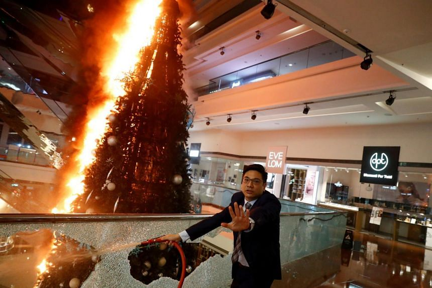 A man reacts as he tries to extinguish a burning Christmas tree at Festival Walk mall in Hong Kong, China on Nov 12, 2019.