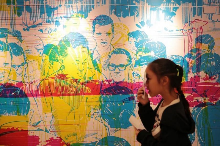 A girl uses coloured lenses to view a mural at the Founders' Memorial Design Showcase.