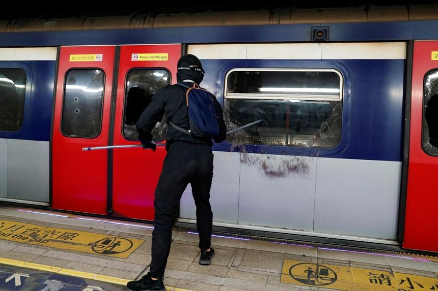 An anti-government protester vandalises a train at the University MTR station during a protest at the Chinese University of Hong Kong, on Nov 13, 2019.