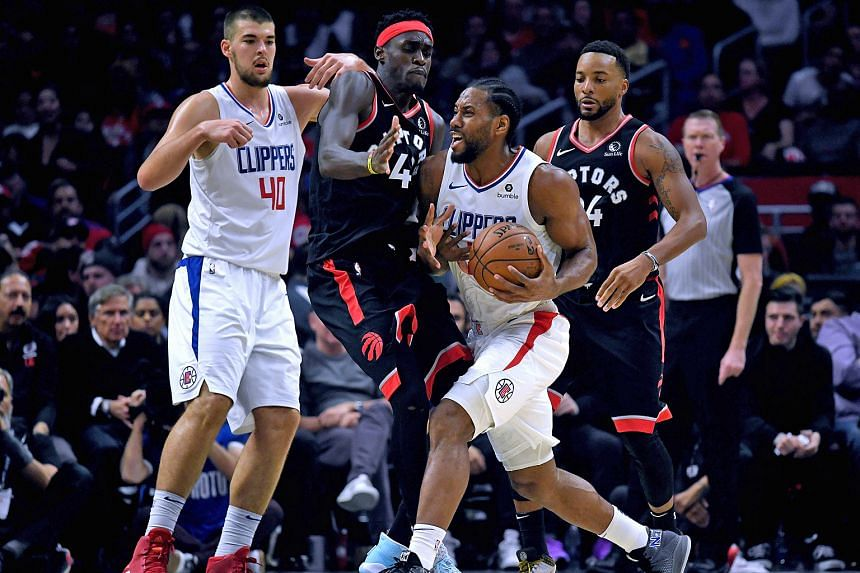LA Clippers' Kawhi Leonard finding his path to the basket blocked by Toronto's Pascal Siakam during their NBA game on Monday. The Clippers won 98-88. PHOTO: AGENCE FRANCE-PRESSE