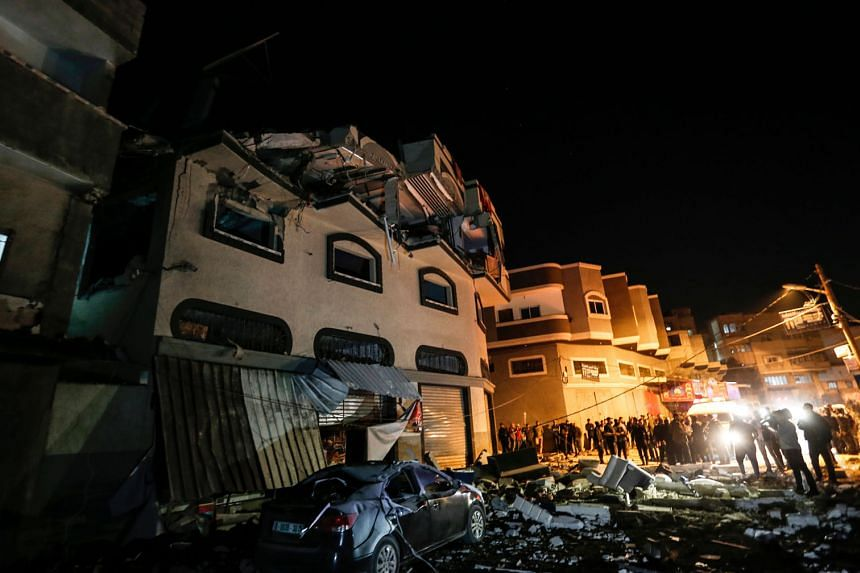 Palestinians inspecting the damaged house of Islamic Jihad commander Baha Abu al Ata yesterday. He and his wife were killed by Israeli rockets that had zoomed in on their bedroom in the three-story house in Sadjaijah, Gaza. PHOTO: AGENCE FRANCE-PRESS