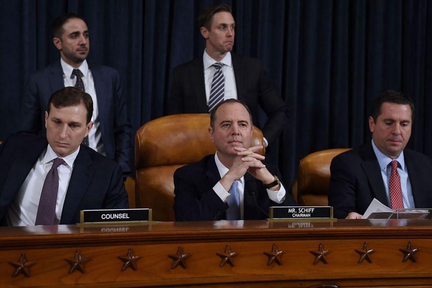 US House Intelligence Committee chairman Adam Schiff (centre) looks on.
