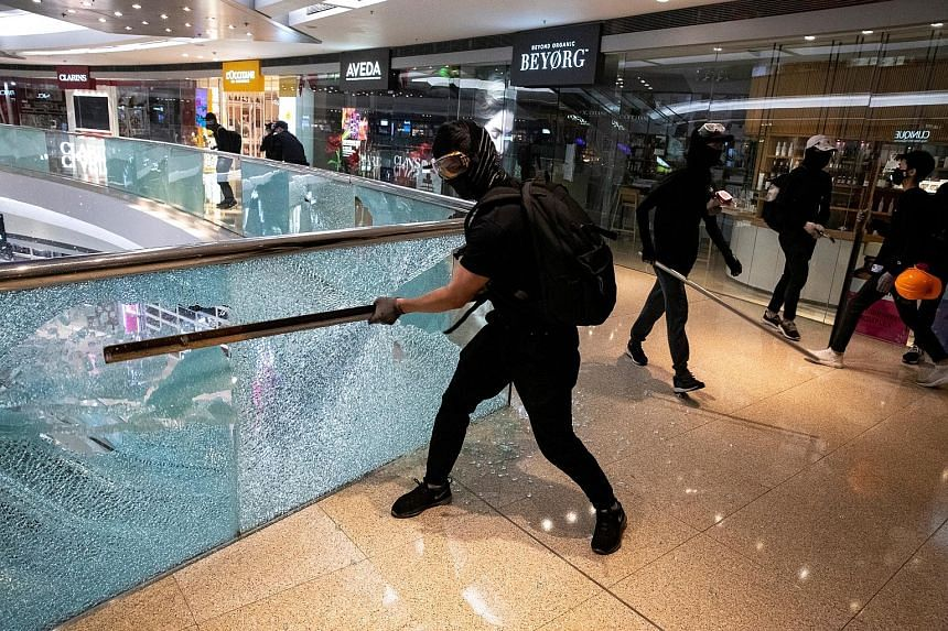 Protesters vandalising Festival Walk (far left) in Kowloon Tong, Hong Kong, on Tuesday. In a separate incident, a fire broke out at a unit next to a DBS branch (left) in the city. PHOTOS: REUTERS, RICHARD LIM/FACEBOOK