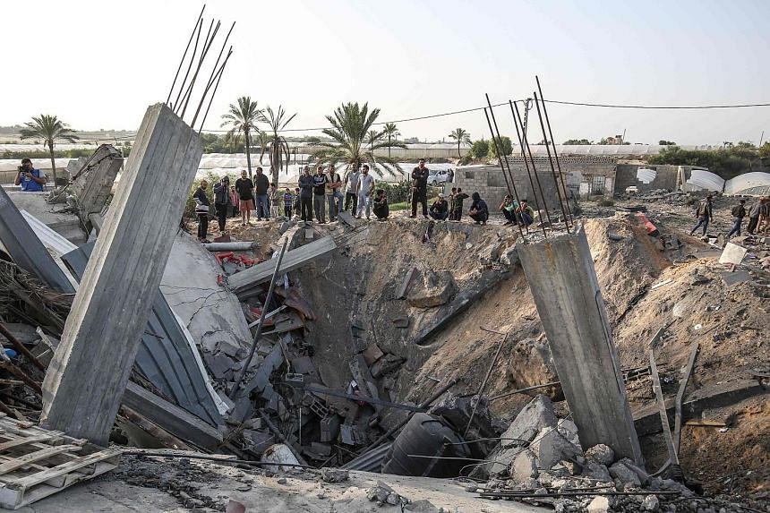Palestinians gathering around the remains of a house destroyed in an Israeli air strike in Khan Yunis, in the southern Gaza Strip, yesterday. Israel killed Palestinian militant Baha Abu al-Ata and his wife Asma on Tuesday, prompting barrages of rocke
