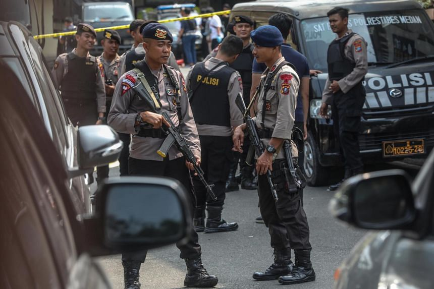 Police officers inspect and stand guard at the scene of a suicide bombing at the police headquarters in Medan, on Nov 13, 2019.