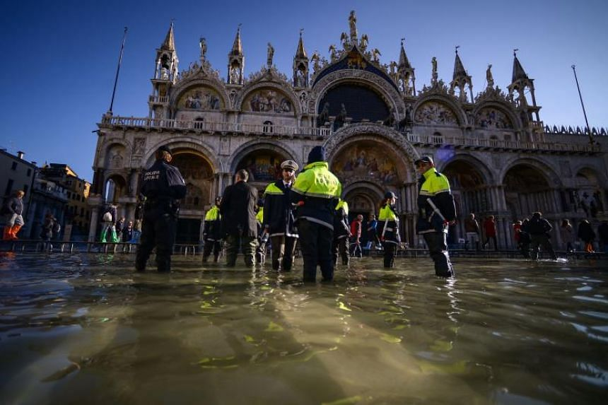 Members of the municipal police stand by St Mark's Basilica on the the flooded St Mark's Square in Venice, on Nov 14, 2019.