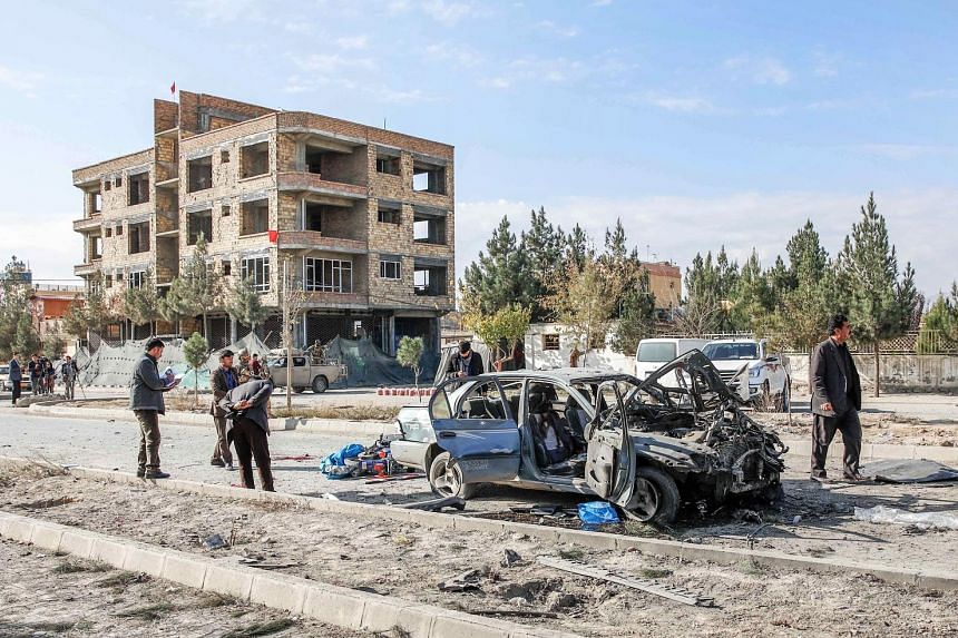 Afghan security forces at the site of the bomb blast, which targeted a convoy of Ministry of Interior Affairs advisers, in Kabul on Wednesday.