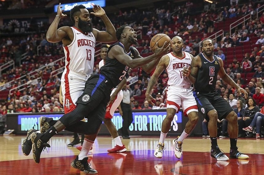 Los Angeles Clippers guard Patrick Beverley trying to score after getting past Houston Rockets guard James Harden during their NBA game at the Toyota Centre on Wednesday night. The Rockets won 102-93 to improve to 8-3. PHOTO: REUTERS