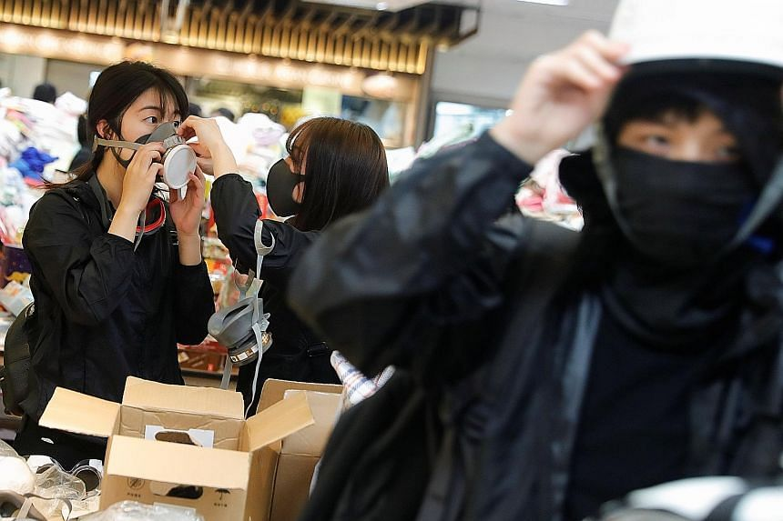 Protesters trying on protective gear (left) and making Molotov cocktails (below) at the Hong Kong Polytechnic University yesterday. Across the city, scenes like these were repeated at nearly half a dozen university campuses. PHOTOS: REUTERS, AGENCE F