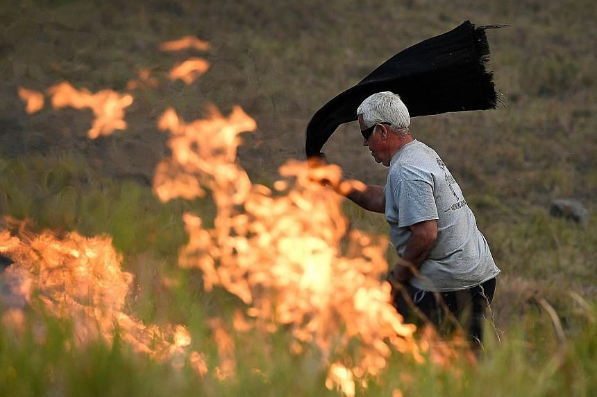 A man using a wet towel to put out flames as they encroached on farmland near the town of Taree, some 350km north of Sydney, yesterday. The death toll from bush fires in eastern Australia has risen to four after a man's body was discovered in a scorc
