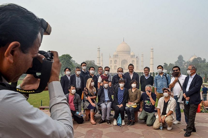 Tourists wearing masks during their visit to the Taj Mahal in India amid heavy smog conditions yesterday. An annual report on the impact of climate change on human health says that people in cities are already suffering premature disease and death fr