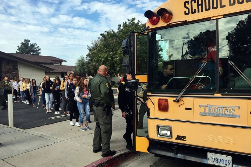 Students are escorted onto a waiting bus following a shooting at Saugus High School.