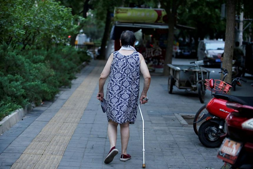An elderly woman walking with a stick along a street in downtown Beijing, China, on July 30, 2019.