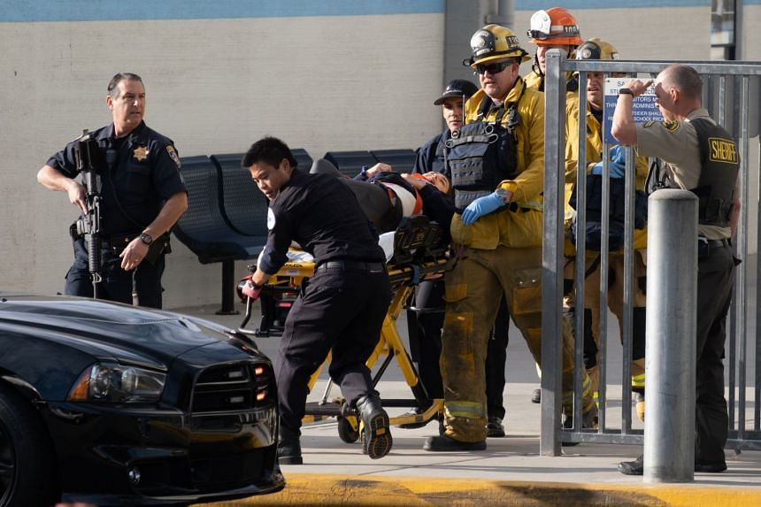 Emergency personnel push a victim away from the scene at Saugus High School in Santa Clarita, California, about 65km north of Los Angeles.