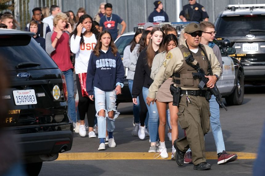 A security officer escorts students from the scene of the shooting.