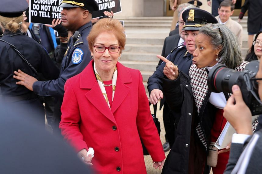 A woman shouts encouragement to US former ambassador to Ukraine Marie Yovanovitch as she departs after testifying.