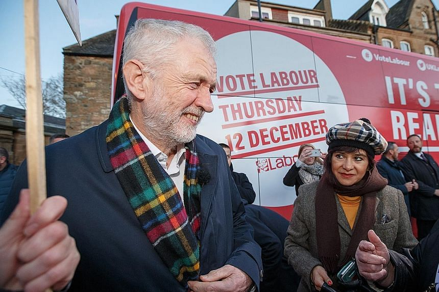 Labour leader Jeremy Corbyn and his wife Laura Alvarez on the campaign trail in Linlithgow, Britain, on Thursday. He remains conflicted about his party's European policy. PHOTO: EPA-EFE British Prime Minister Boris Johnson during a general election c