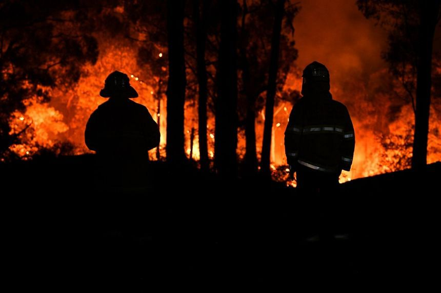 Firefighters watch on as the Gospers Mountain fire approaches a property at Colo Heights, north-west of Sydney, on Nov 15, 2019.