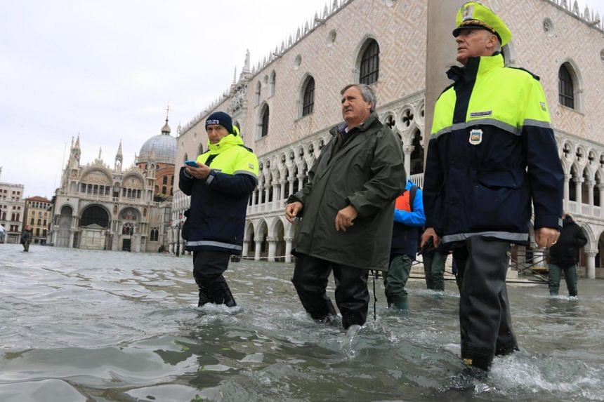Venice Mayor Luigi Brugnaro (centre) wades through high water in Venice, Italy on Nov 15, 2019.