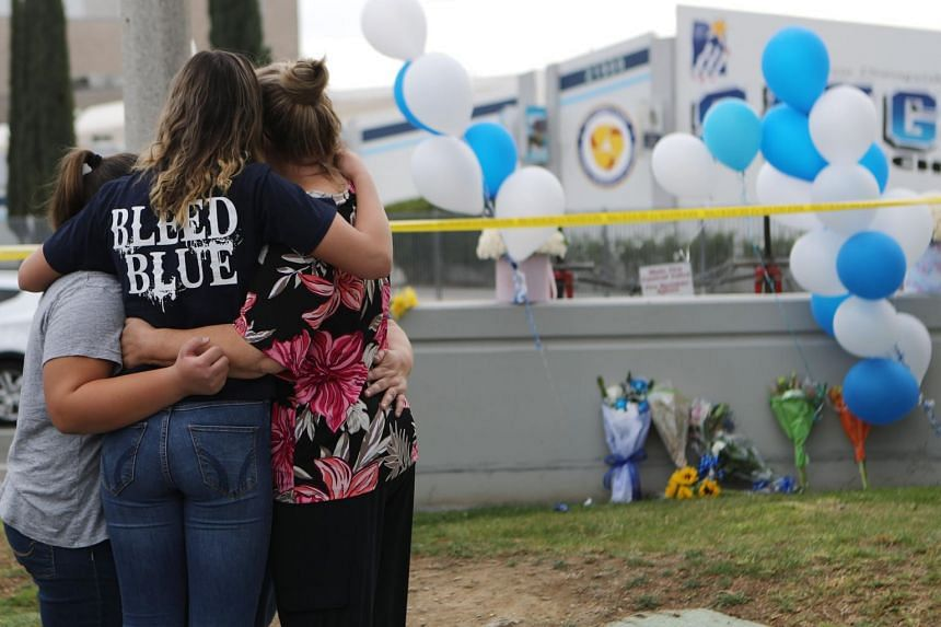 A Saugus High School student is embraced as she visits a makeshift memorial in front of the school for victims of the shooting, on Nov 15, 2019, in Santa Clarita, California.
