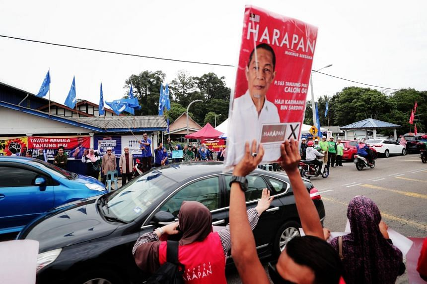 Supporters for Pakatan Harapan and Barisan Nasional occupied both sides of the road near SK Telok Kerang polling centre on Nov 16, 2019.