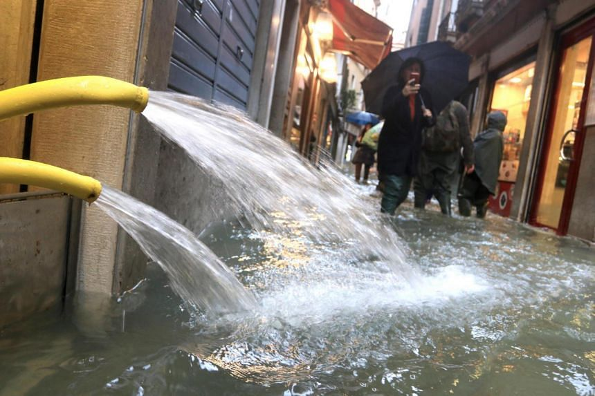 People wade through high water in Venice, Italy on Nov 15, 2019. 2019.
