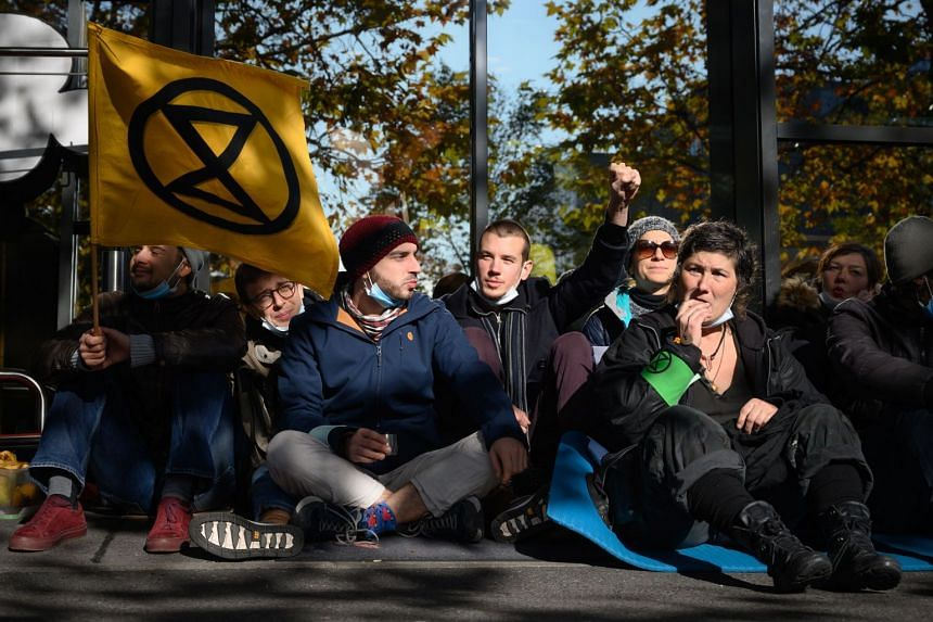 Activists sit blocking an entrance at Geneva airport's private jet terminal.