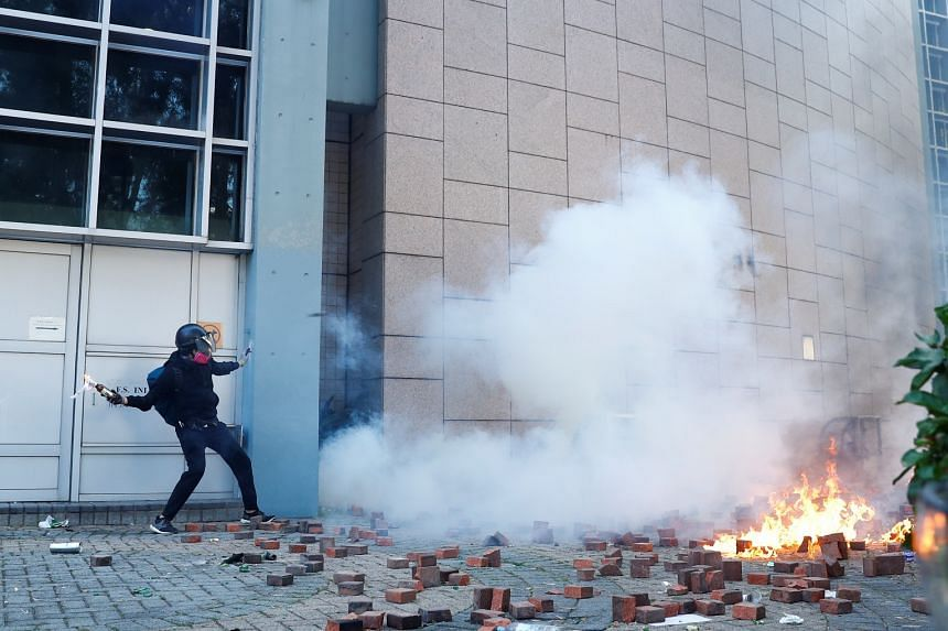 A protester throws a molotov cocktail during clashes with police outside Hong Kong Polytechnic University in Hong Kong on Nov 17, 2019.