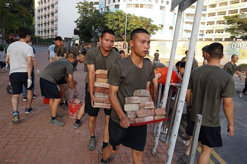 Personnel from the Chinese People's Liberation Army (PLA) barracks in Hong Kong conducting a lightning-quick removal of bricks and debris near their base yesterday. The presence of PLA troops on the streets, even to help clean up roads near their bas