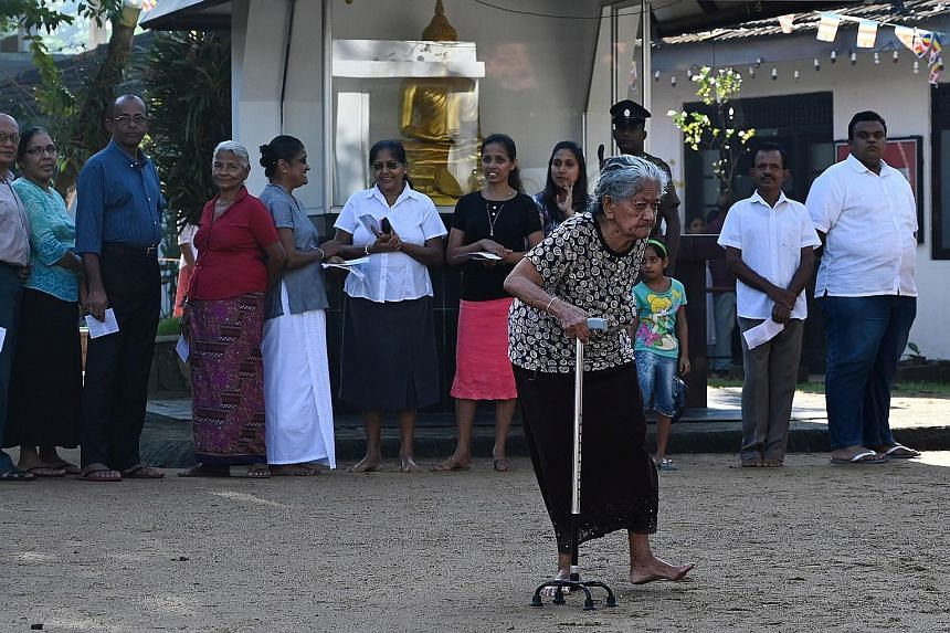 Voters lining up at a polling station in Colombo yesterday.
