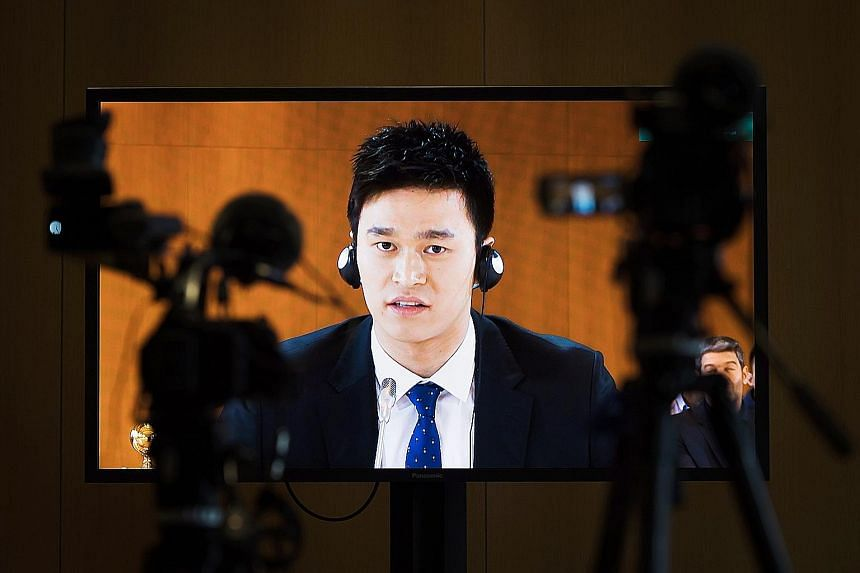 Sun Yang is pictured on a TV screen during the public hearing on Friday. The CAS will deliberate and set out its decision on a later date.
